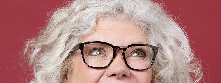 Older woman wearing glasses on red background