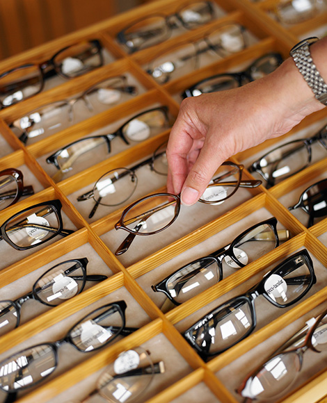 Woman picking up glasses from glasses display