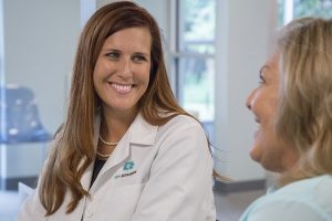 Dr. Compton speaking and smiling with a patient