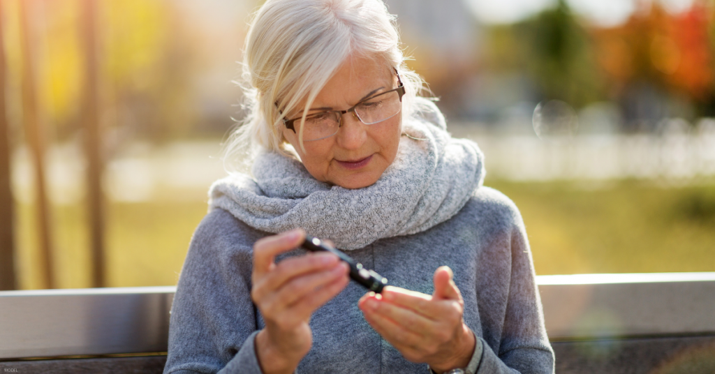 A woman tests her blood sugar levels at the park.